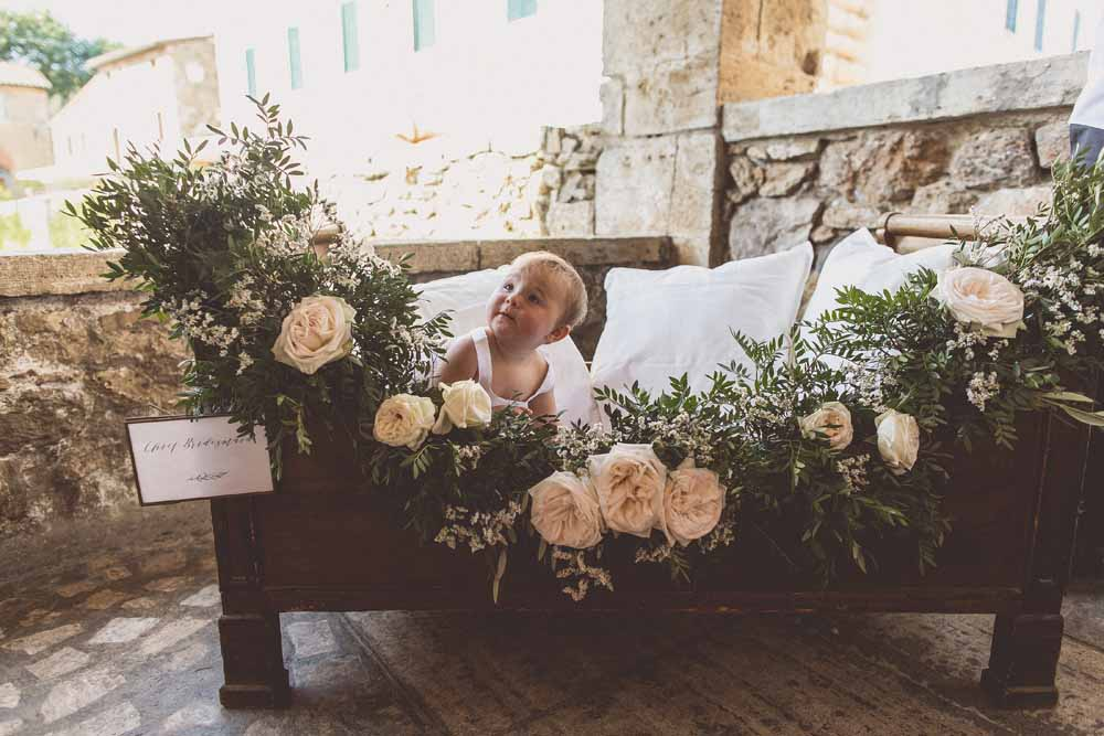 Flower girl cot wedding ceremony with floral garland by Passion for Flowers