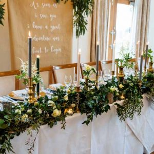 op-table-flowers-long-garlands-of-foliage-white-green-flowers-gold-candlesticks-Passion-for-Flowers