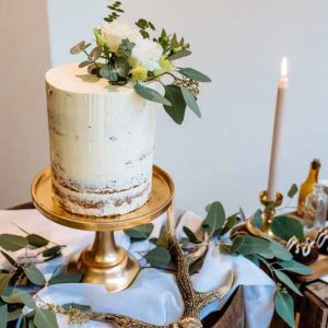Wedding-cake-table-gold-cake-stands-and-foliage-to-top-of-cake