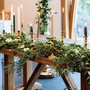 Wedding-ceremony-table-foliage-garlands-gold-candle-stick