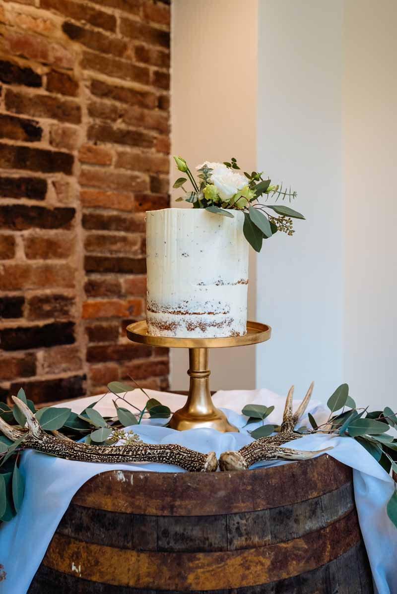 simple-white-and-gold-wedding-cake-with-foliage-to-top