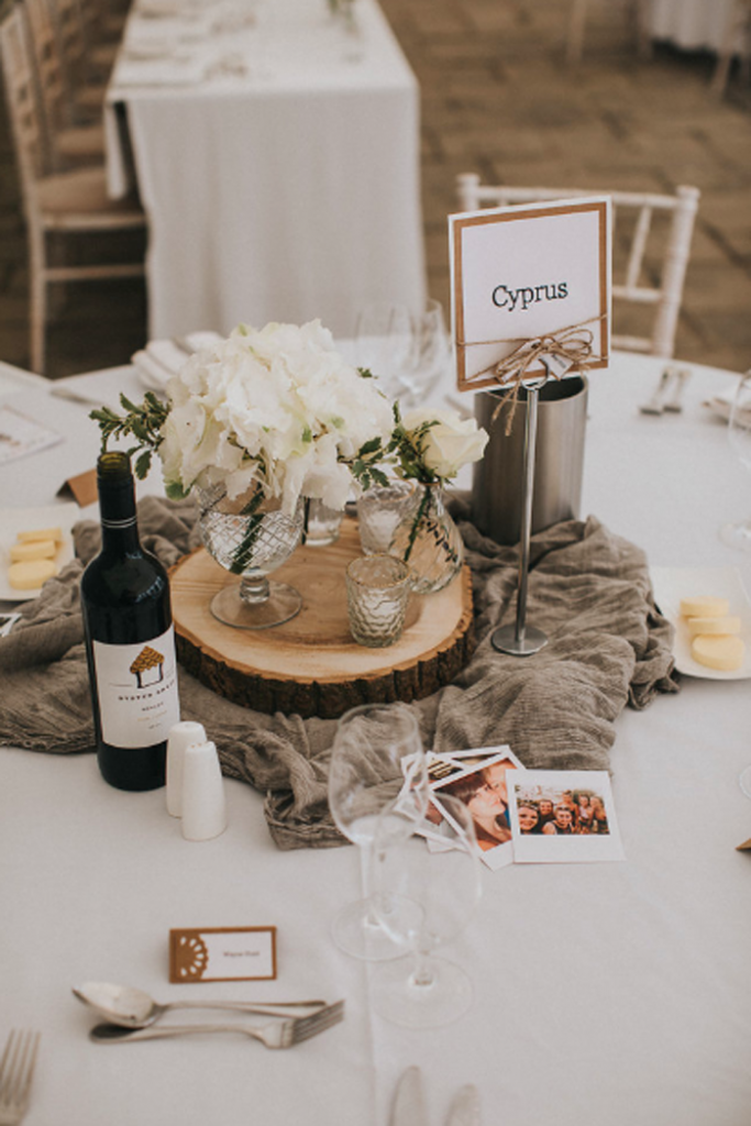 Rustic elegant centrepieces tree slices with gass vases and grey runner Birtsmorton Court Marquee wedding