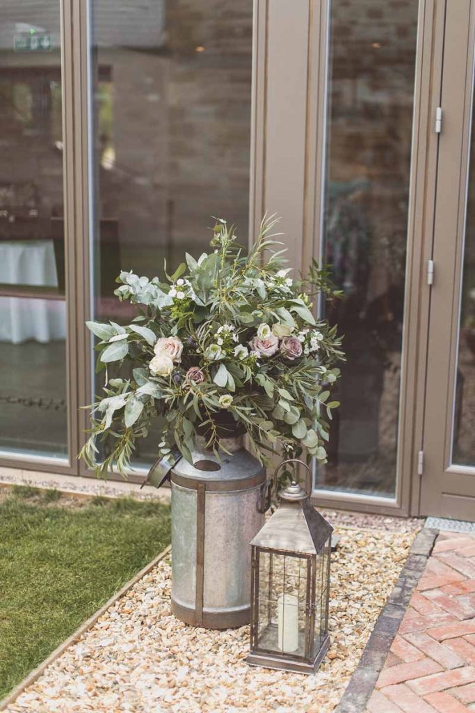 Large milk churn entrance wedding flowers Blackwell Grange rustic barn wedding venue florist Passion for Flowers