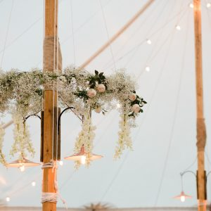 hanging flowers in marquee around poles