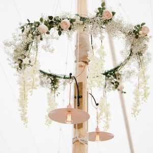 marquee wedding hanging hoop of flowers around poles