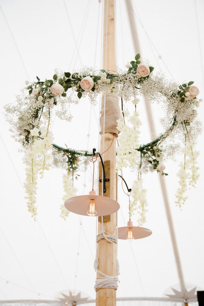 marquee wedding hanging hoop of flowers around poles