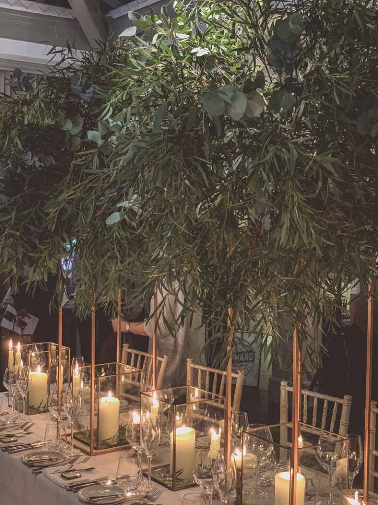 Gold floral stands of foliage above bronze nrass lanterns long wedding table styling Passion for Flowers Hampton Manor wedding florist