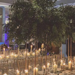Gold floral stands of foliage above bronze nrass lanterns long wedding table styling Passion for Flowers Hampton Manor wedding florists