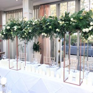 suspended flowers over gold floral frames top table hampton manor