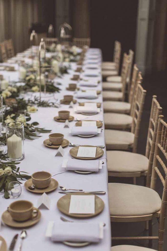 Long wedding tables flower garlands and cylinder vase candles Hampton Manor Passion for Flowers