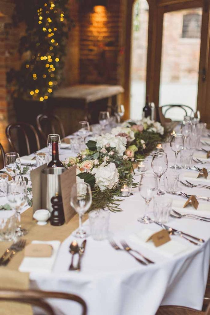 Oval long tables Shustoke Farm Barns hessian table runners hydrangea and rose garlands