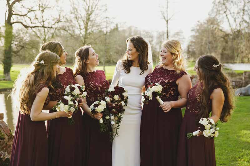 Winter wedding bridesmaids deep burgundy dresses with rose bouquets