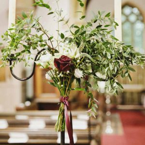 Winter wedding pew end alternatives bunch of roses foliage on candlesticks Passion for Flowers Birtsmorton Court
