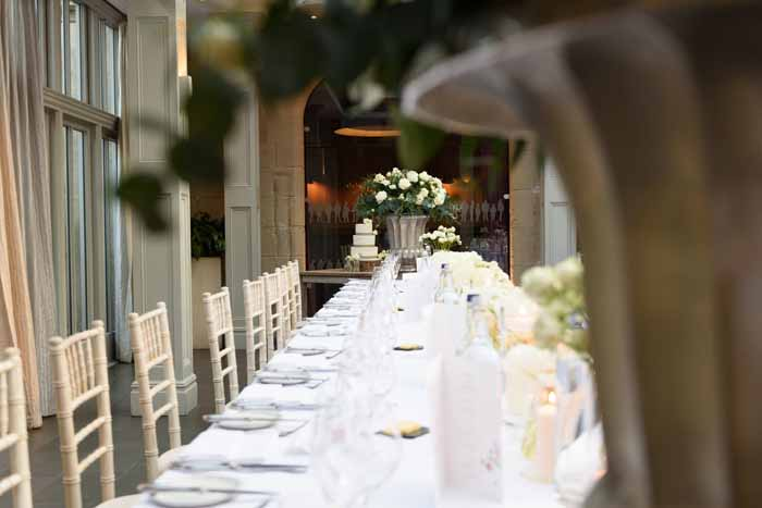Large urns either end of long tables Hampton Manor wedding flowers