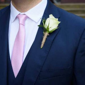Navy grooms suit pink tie cream rose buttonholes