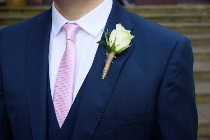 Navy grooms suit pink tie cream rose buttonholes