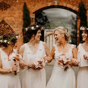 Bridesmaids cream dresses blush pink rose bouquets and flower crowns
