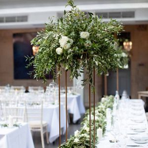 Tall bronze floral stands wedding centrepieces with full garlands for top table