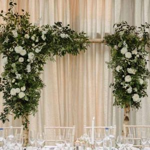 Wedding backdrops asymmetric arch behind top table - Passion for Flowers